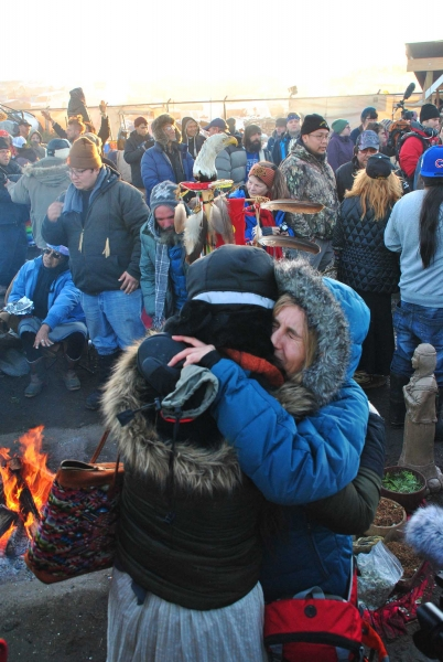 Activists hug each other during celebration of Standing Rock victory - photo by C.S. Hagen